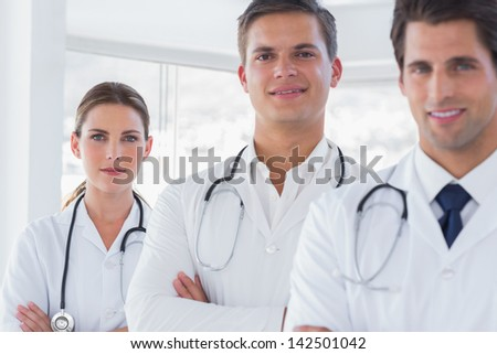 Three smiling doctors with arms crossed and lab coats