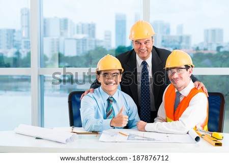 Three smiling engineers at the table - stock photo