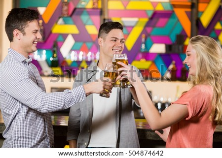 Three smiling friends toasting glasses of beer in bar