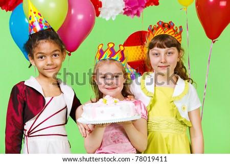Three smiling girls holding birthday cake - stock photo
