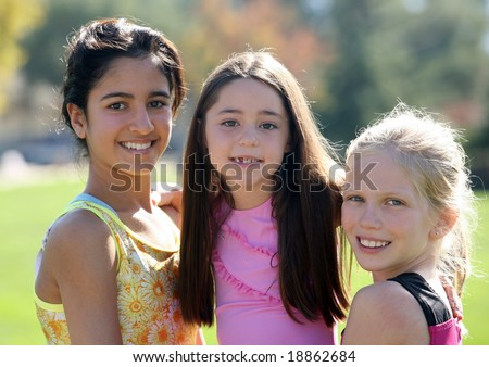 Three smiling girls of different race and age - stock photo