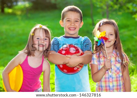 Three smiling kids in a summer park - stock photo