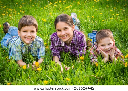 Three smiling kids lying together on green grass meadow - stock photo