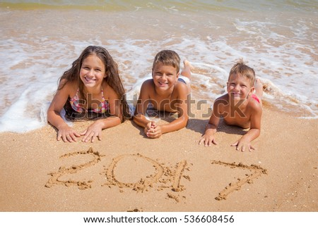 Three smiling kids on beach lying down on the sand near water with new year 2017 sign