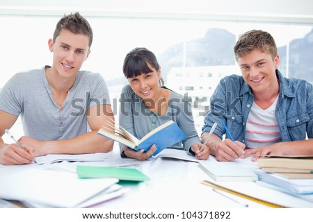 Three smiling students doing homework together as they all look into the camera - stock photo
