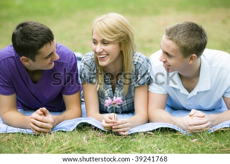 Three Smiling Teens Lying on Blanket in a Park - stock photo