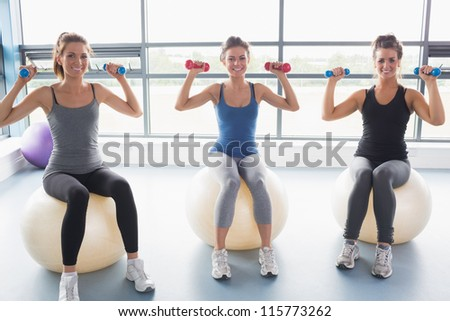 Three smiling women sitting on exercise balls and lifting weights in a gym - stock photo