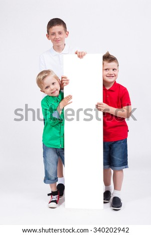 Three smiling young students on a white background held vertically white poster and looking at the camera - stock photo