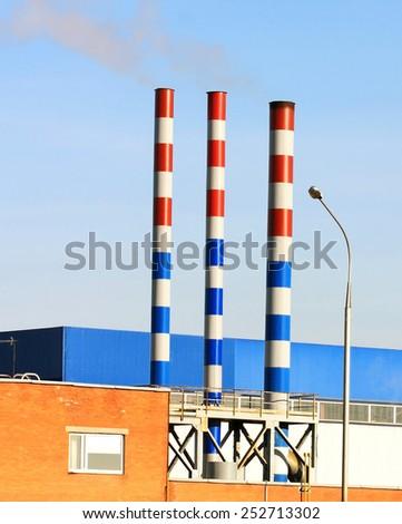 Three smokestacks smokestacks of an industrial facility - stock photo