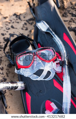 Three Snorkeling Sets for Family. Masks and Flippers on Sand. - stock photo