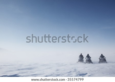 Three snowmobiles on a blowing barren winter landscape