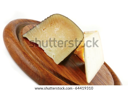 three soft delicatessen cheeses on wooden plate