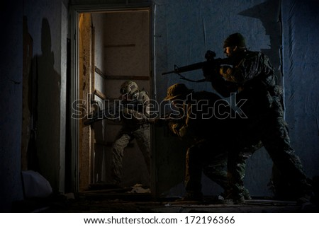 Three soldiers in full uniform stormed the building at night. Hostage rescue operation. - stock photo