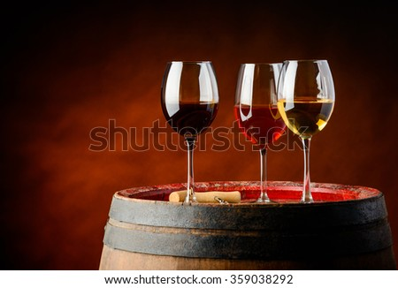 Three sorts of wine on a barrel in a winery. red, rose and white wine - stock photo
