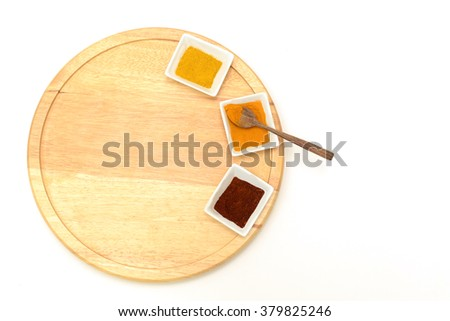 Three spices on wooden lazy susan with spoon, top view - stock photo