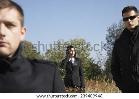 Three Spies Standing in Wasteland - stock photo