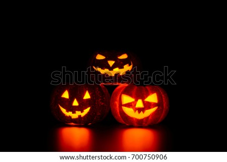 Three spooky carved pumpkins on table in darkness