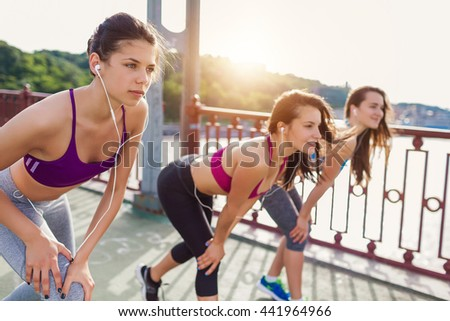 Three sportive pretty women stretching before their run - on city bridge at sunset. Sporty friends portrait - stock photo