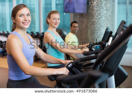 Three Sporty People Riding Exercise Bikes in Gym