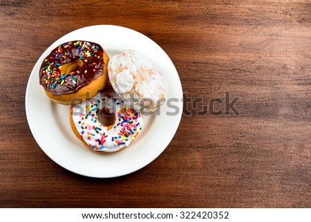 three Stacked doughnuts on brown table. Chocolate, White, Creme filled. - stock photo