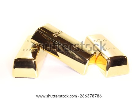 three stacked gold bars on a light background - stock photo