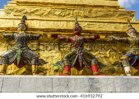 Three Statues of Giant Guardians in front of the golden pagoda at Wat Phra Keaw temple (Emerald Buddha), Bangkok,Thailand - stock photo