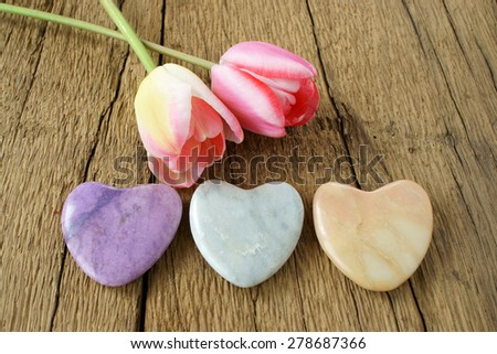 Three stone hearts and two tulips on a rustic wooden plank - stock photo