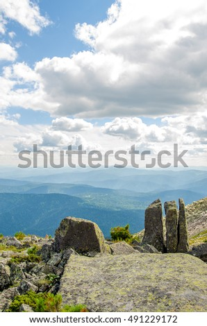 three stones on top of the mountain. in the high mountains clouds float. colorful mountain and cumulus clouds. mottled mountain rocks. rock variegated color.