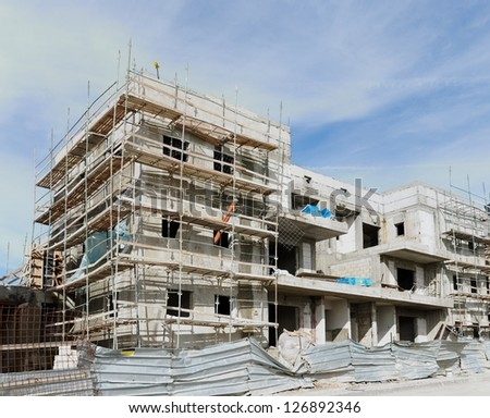 Three-storeyed apartment building under construction - stock photo