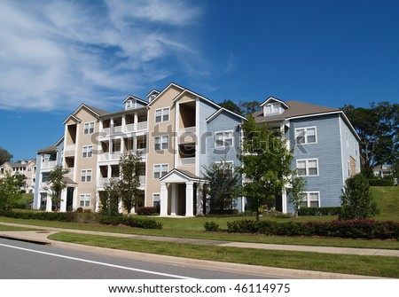 Three story condos, apartments or town homes with vinyl siding of blue and tan. - stock photo