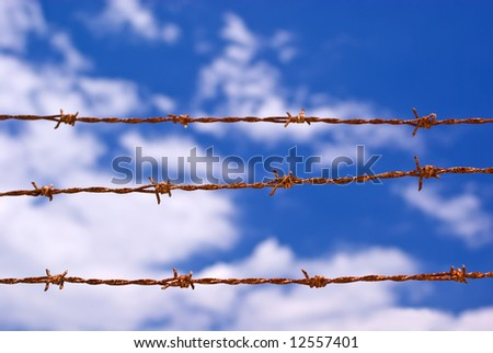 Three Strands of Sunbaked Barbed Wire Against Partly Cloudy Blue Sky - stock photo