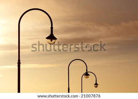 Three street lanterns over the orange sunset sky - stock photo