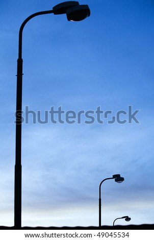 Three streetlights/street lamps at sunrise (color toned image; selective focus ) - stock photo