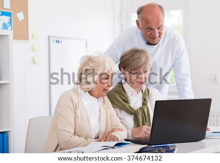 Three students are sitting in front of computer and working