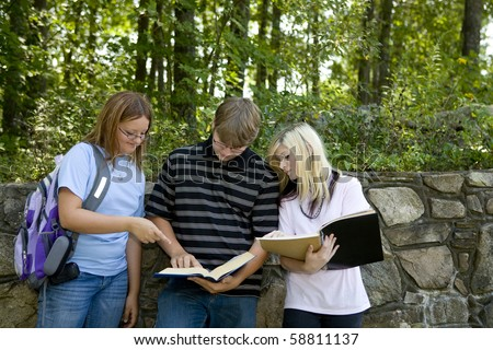 Three students look over their notes from class.