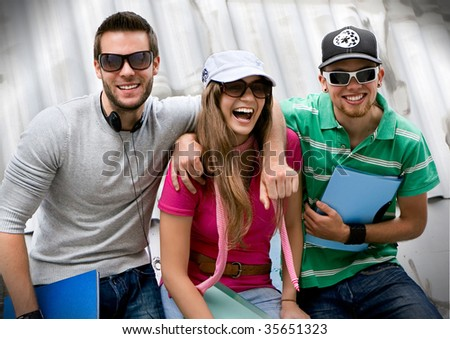 three students standing in front of a graffiti-wall - stock photo