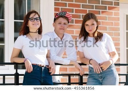 Three students standing on the porch of the college on the background of brick wall - stock photo