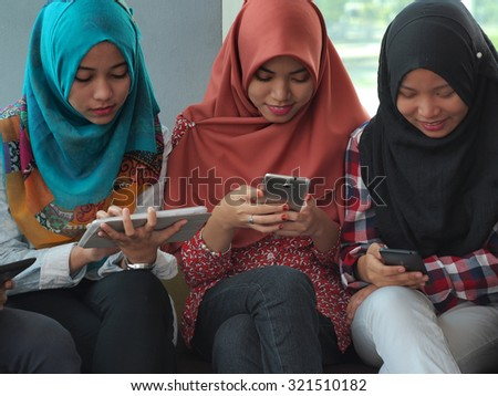 Three students wearing hijabs with mobile devices. - stock photo