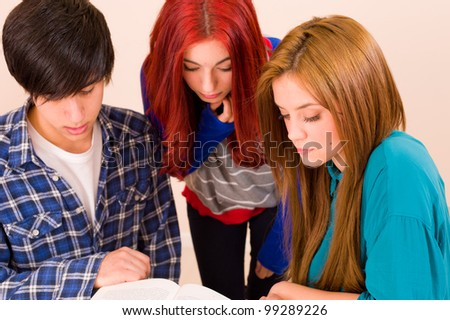 Three students working together over a book