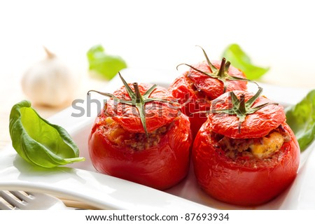 Three stuffed tomatoes on a white plate - stock photo