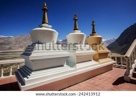 Three stupa and blue sky at Diskit monastery, Ladakh, India - September 2014 - stock photo