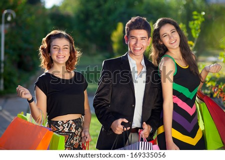 Three stylish teenagers out shopping together standing outdoors laughing and smiling with colourful shopping bags over their arms as they buy their Christmas gifts - stock photo