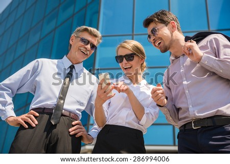 Three successful business people in suits looking at phone. Office background. - stock photo