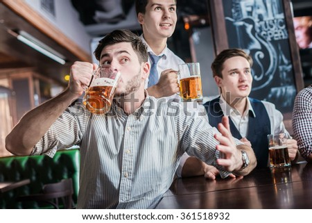 Three successful businessmen drink beer and rejoice and shout together watching TV at the bar. Confident business people having fun with friends at the bar with a beer watching football on TV - stock photo