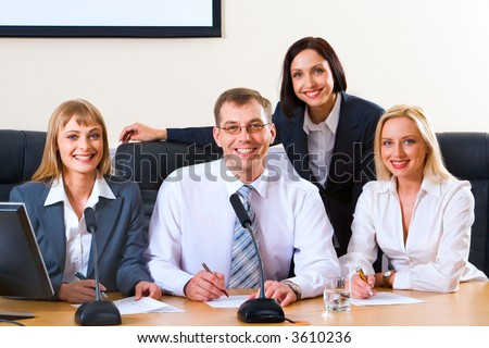 Three successful smiling people sitting in a row in  chairs at the table with monitor, microphones and documents on it and cute business woman standing behind them looking at the camera - stock photo