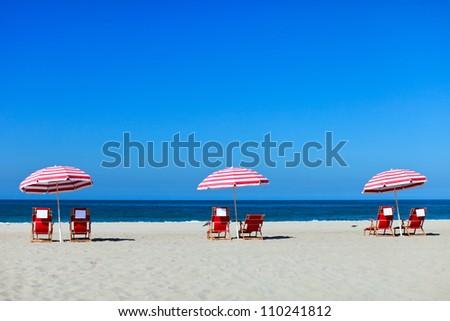 Three sun umbrellas at Santa Monica beach - stock photo