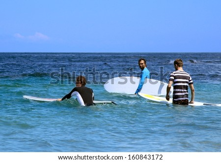 Three surfer enter into the ocean with surf boards to the starting point for riding on the waves - stock photo