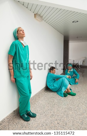Three surgeons taking break in hospital corridor - stock photo