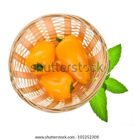 three sweet yellow peppers in a wicker basket are a top view isolated on white background