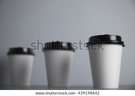 Three take away white paper cups with closed black caps, top view, isolated on simple gray background, first cup in close focus, cups behind are unfocused , bottom view - stock photo